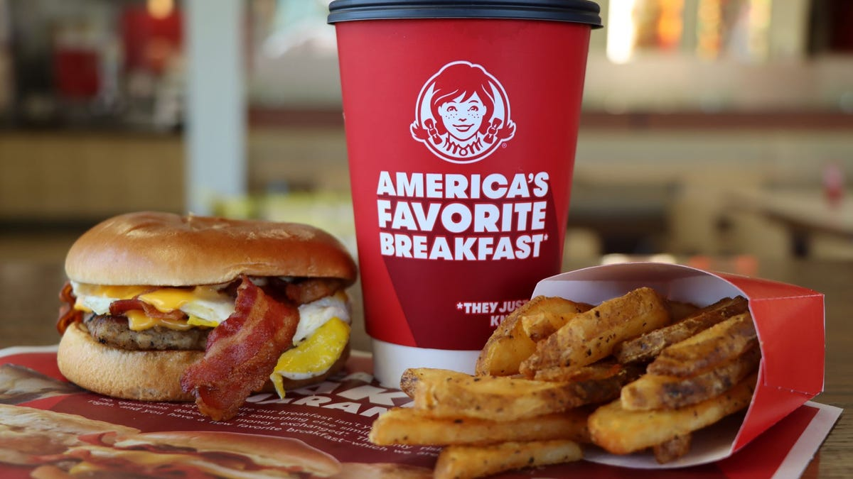 A breakfast biscuit, hash browns, and a coffee cup with the Wendy's logo.