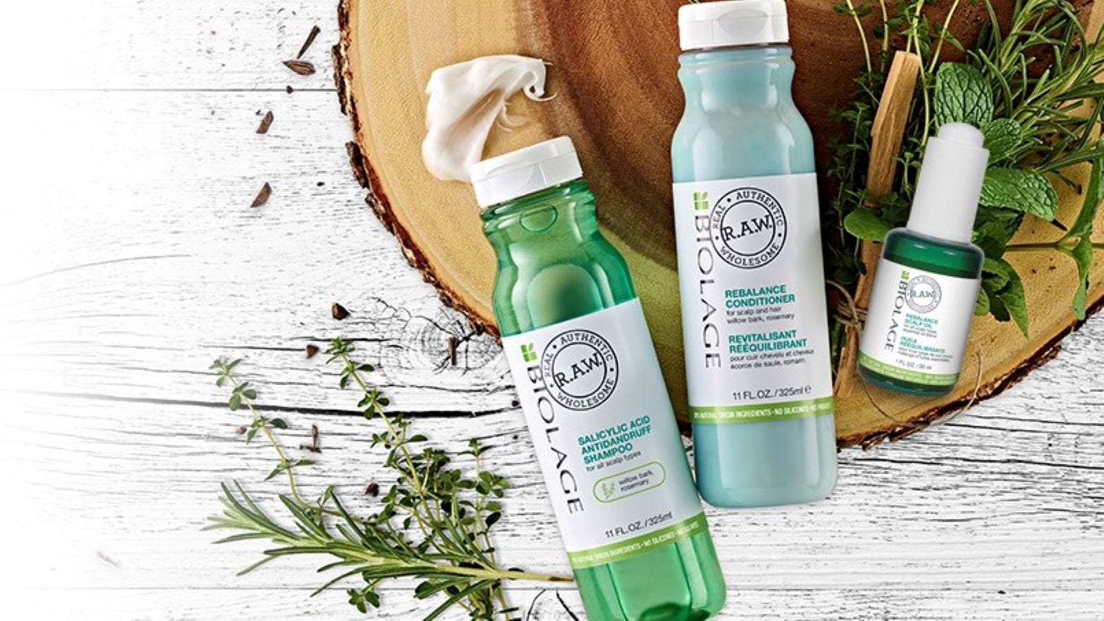The Biolage R.A.W. Shampoo, Conditioner, and Scalp Oil surrounded by green leafy herbs.