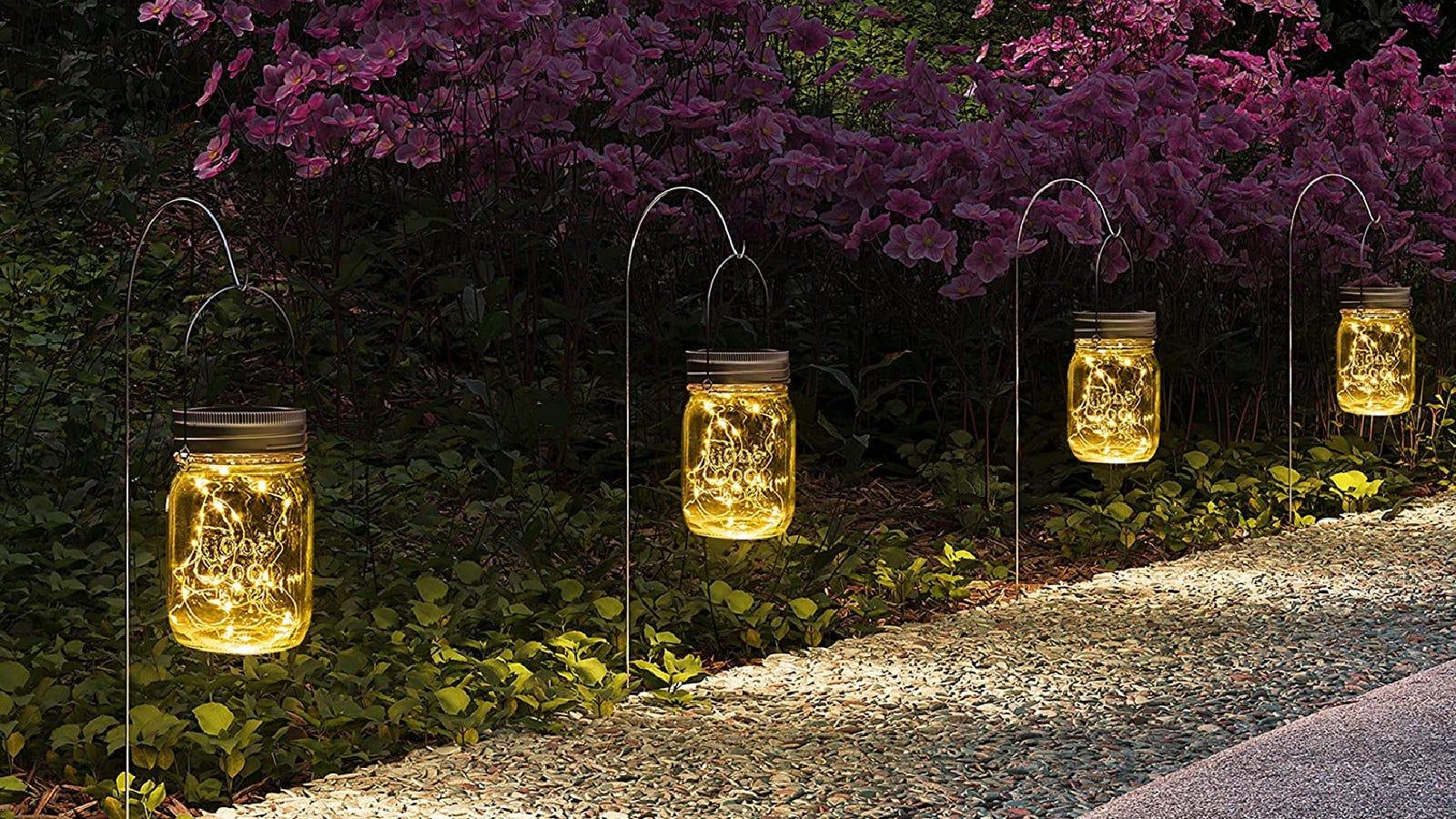 A path lining a bush garden, embellished with glowing Gigalumi jar lanterns at night.