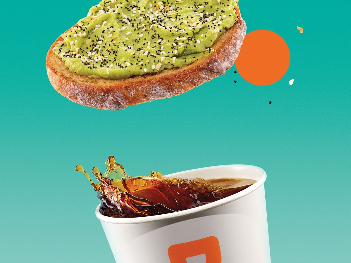 A cup of coffee splashes below a piece of avocado toast.