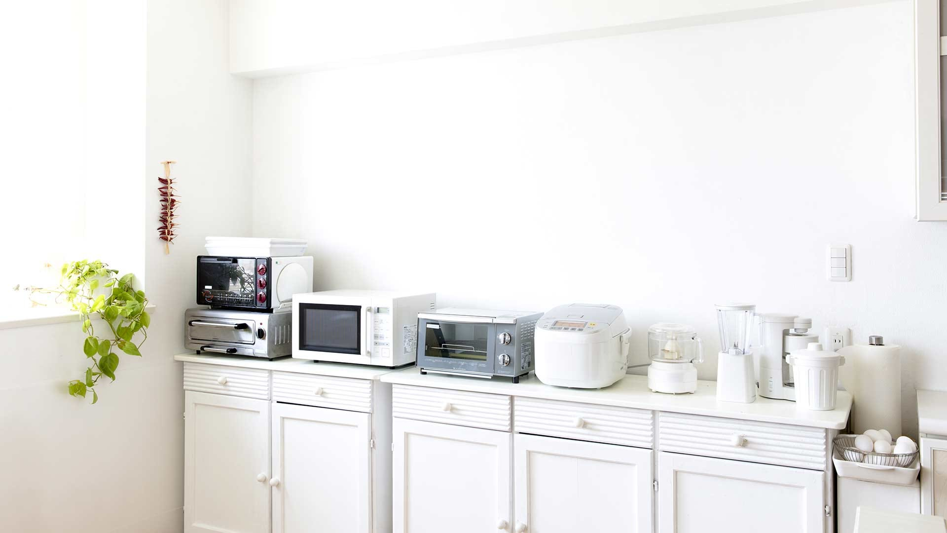 A brightly lit white kitchen with counterspace covered in kitchen appliances.