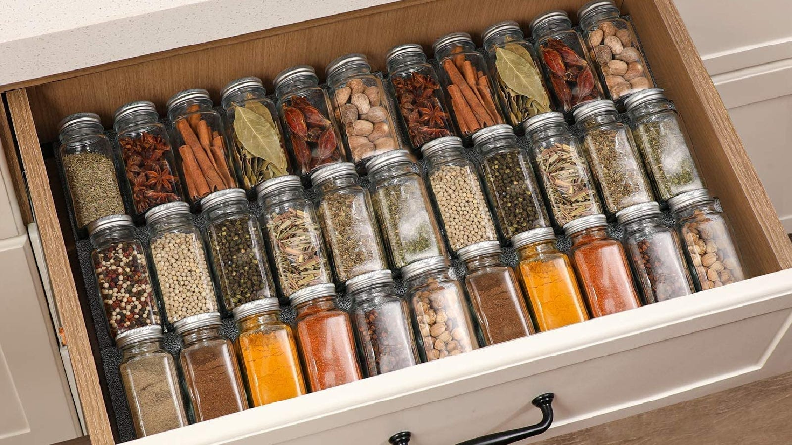 A drawer full of jars filled with dried herbs and spices, featuring jars by Aozita.