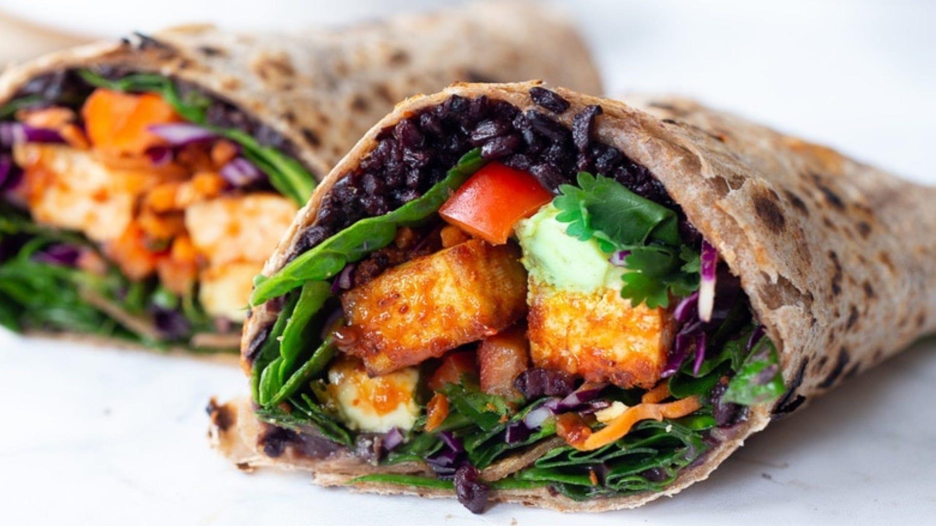 Burrito with black rice, peanut tofu, and greens inside