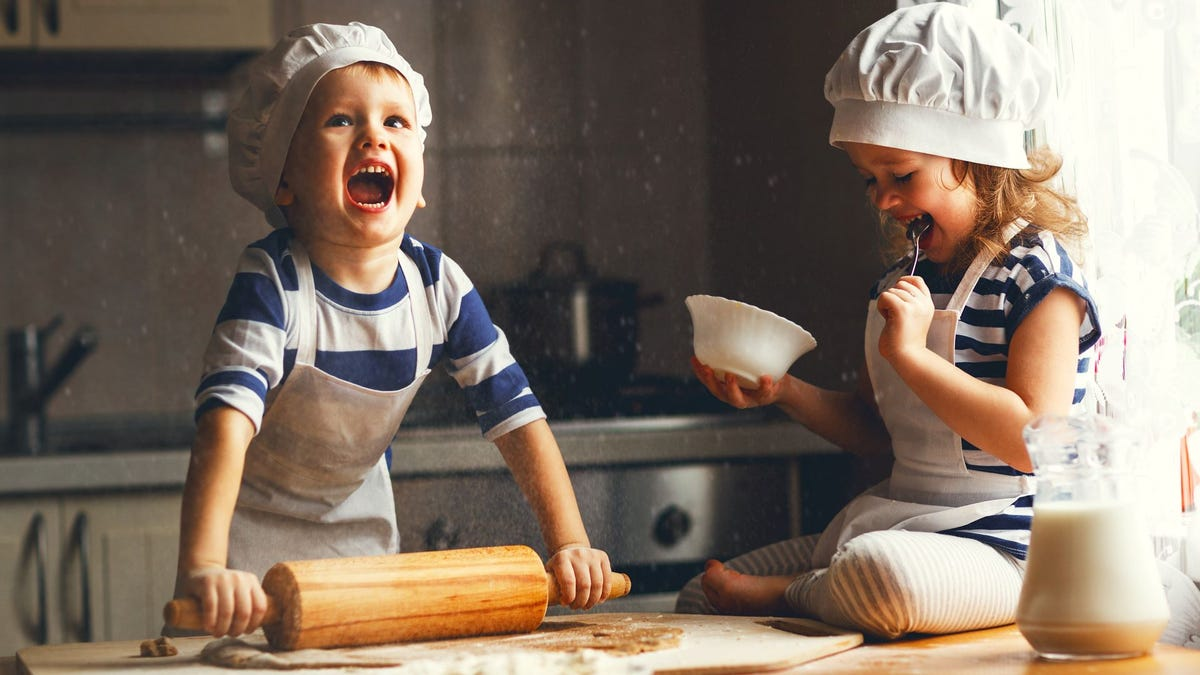 Two kids rolling out dough and wearing chef's hats.