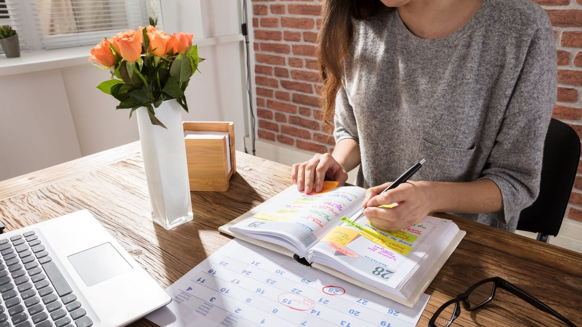 A woman writing something in a hardcover planner.