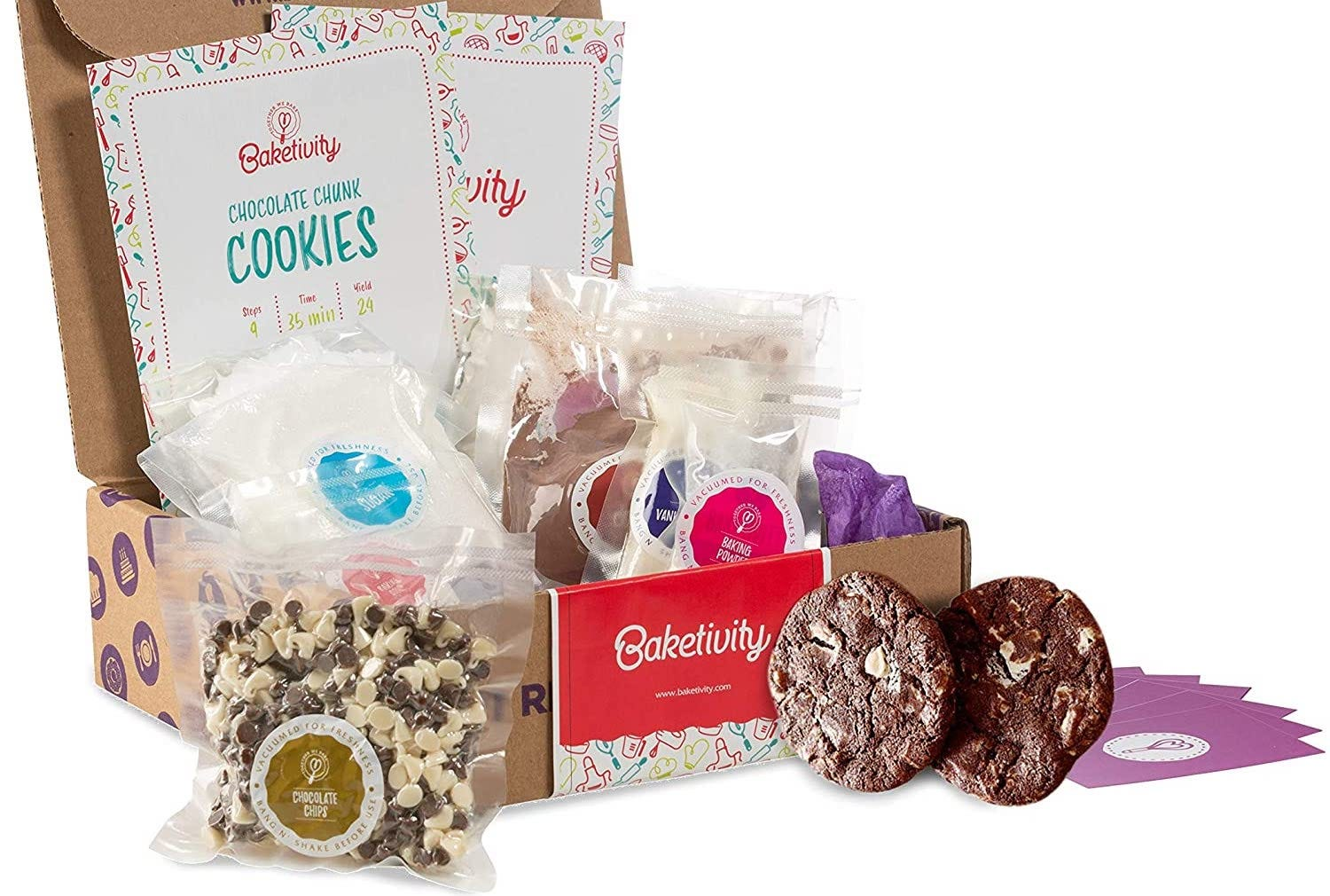 A cardboard box, open to reveal bags of baking supplies, with a bag of chocolate chips and two cookies in front
