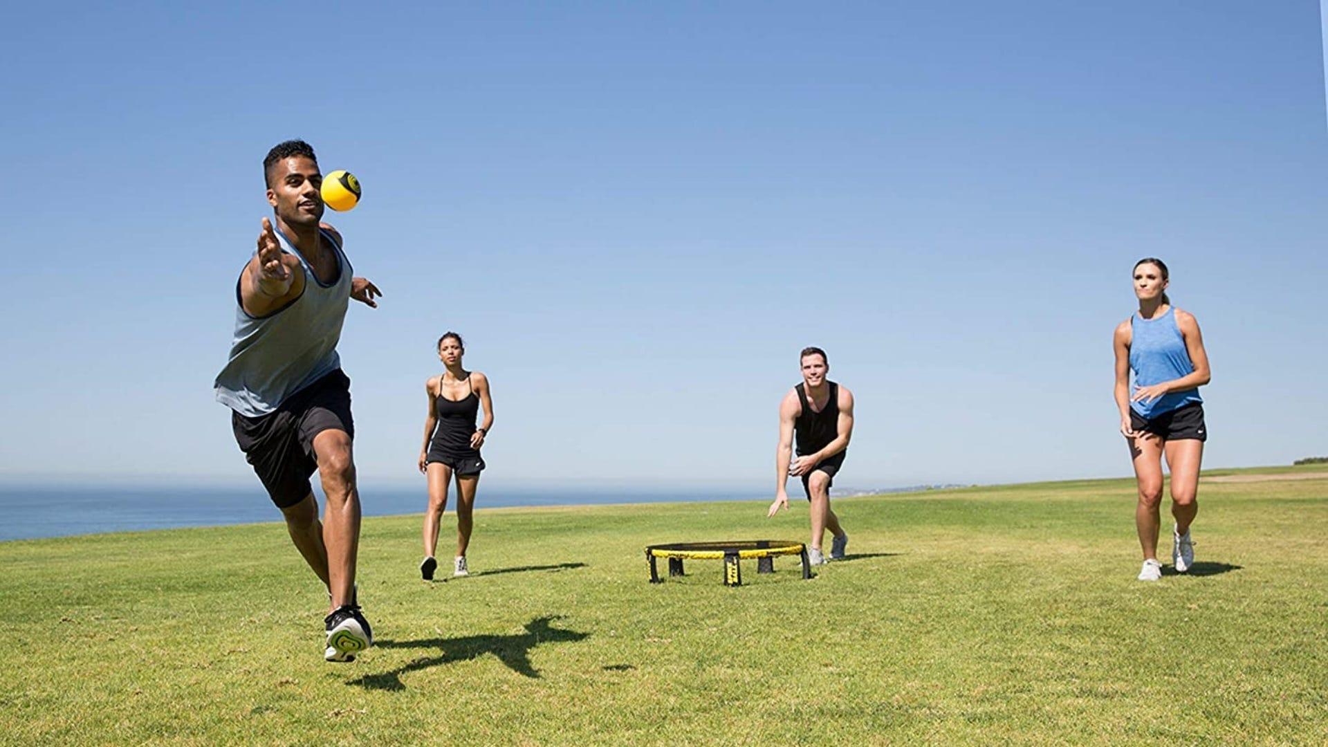 Four people playing Spikeball outside.