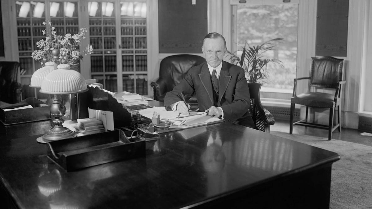 President Calvin Coolidge sitting at his desk in the Oval Office at the White House.