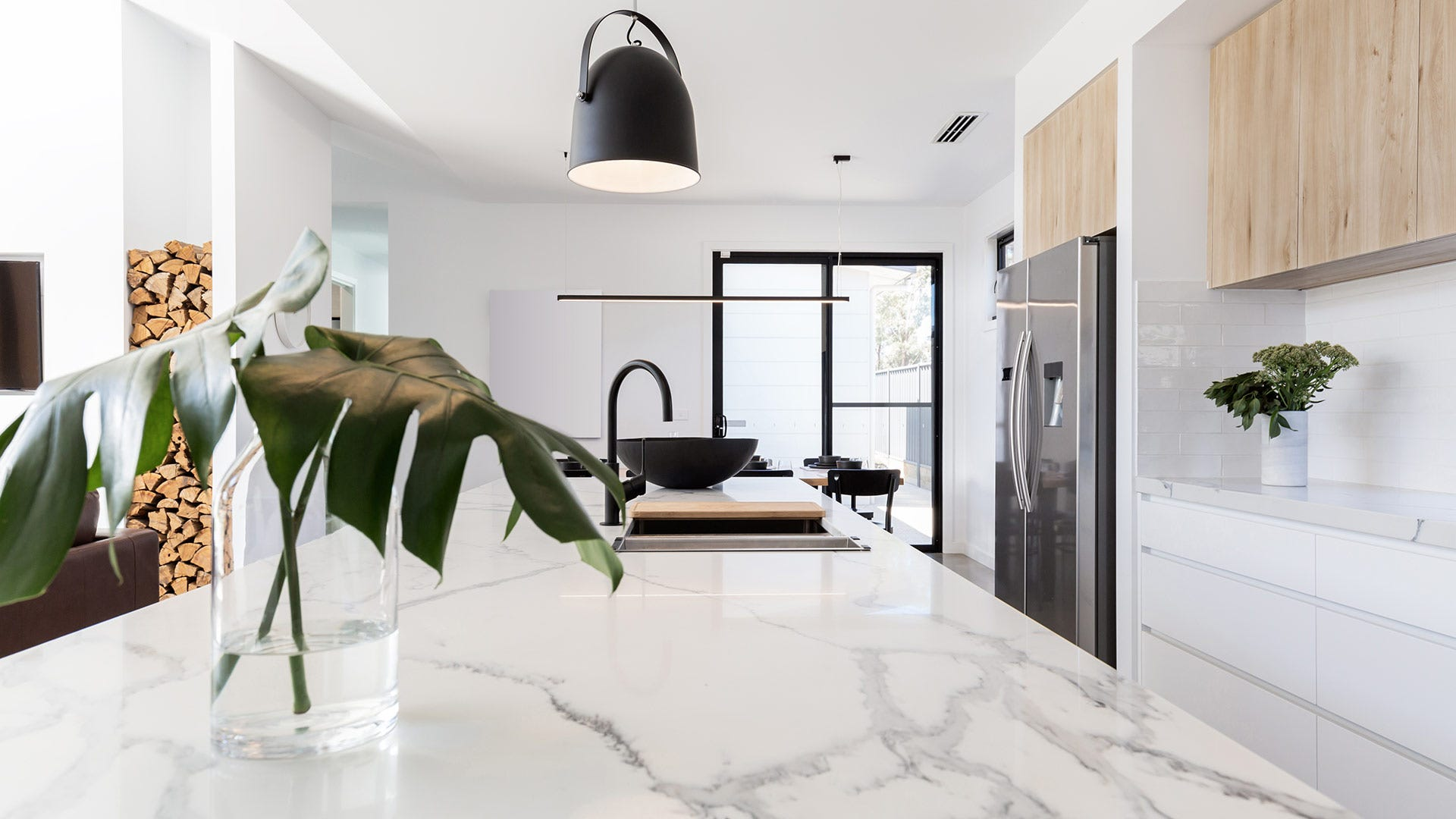 A closeup of white marble counters in a sunny modern kitchen.