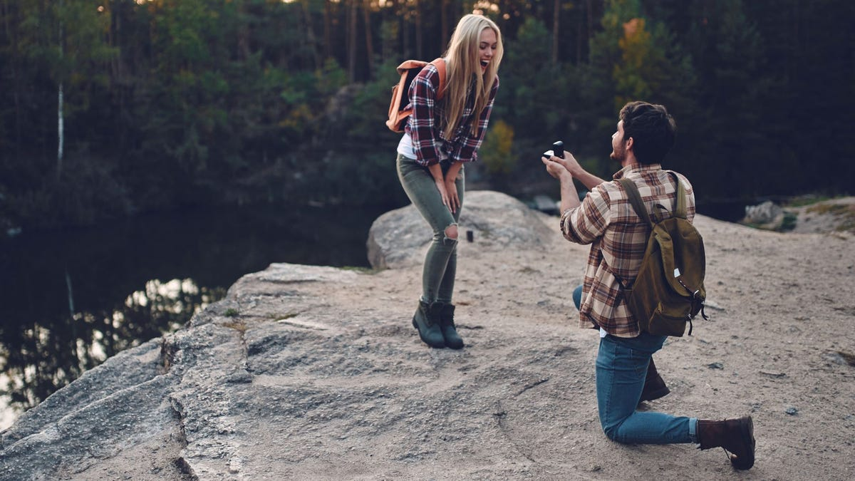 A man on one knee proposing marriage to a woman on a cliff overlooking a river and woods.
