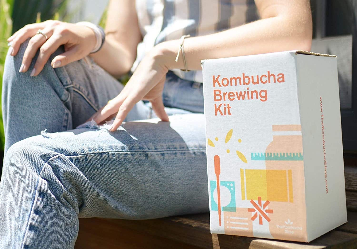 """A box reading """"Kombucha Brewing Kit"""" sits on a bench next to a woman wearing jeans"""