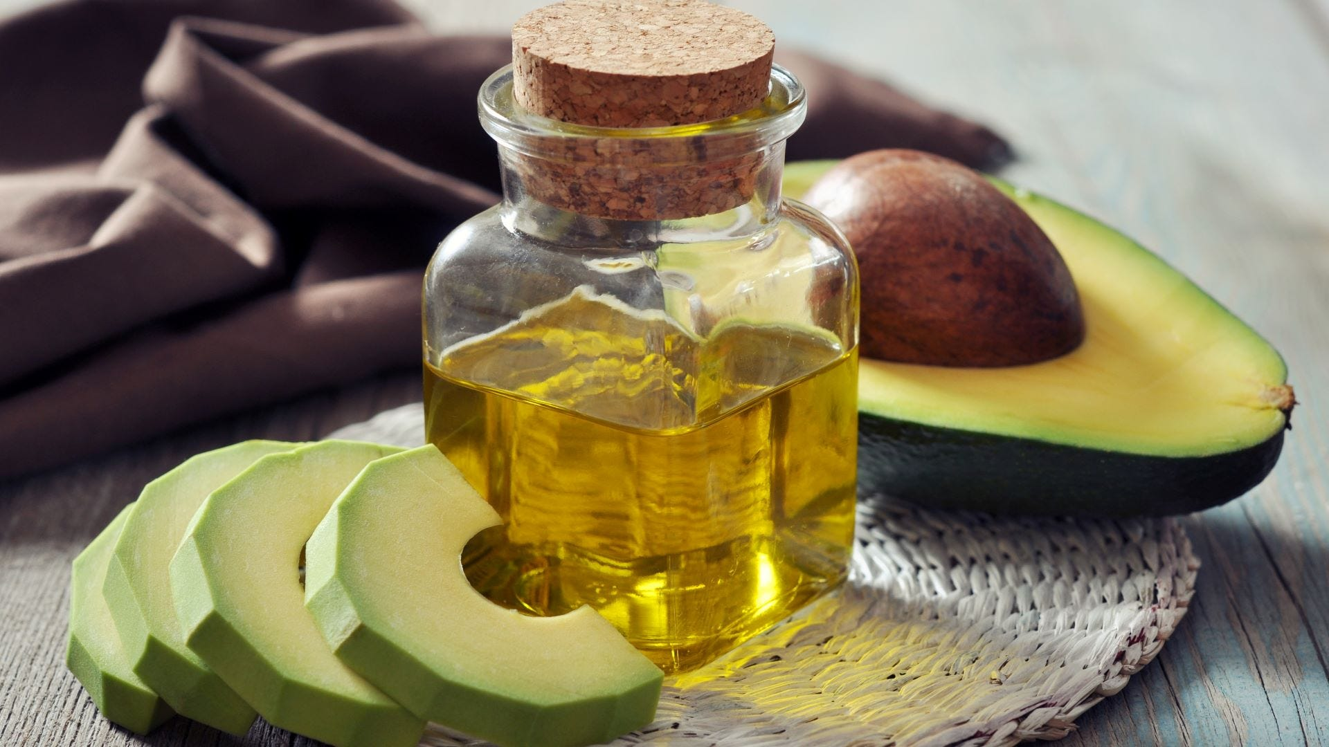 A bottle of avocado oil surrounded by sliced avocado.
