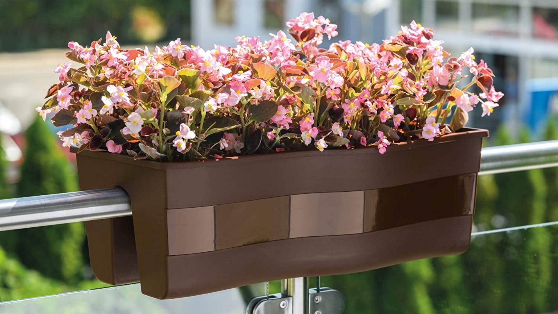 A planter box sits on a balcony railing full of flowers.