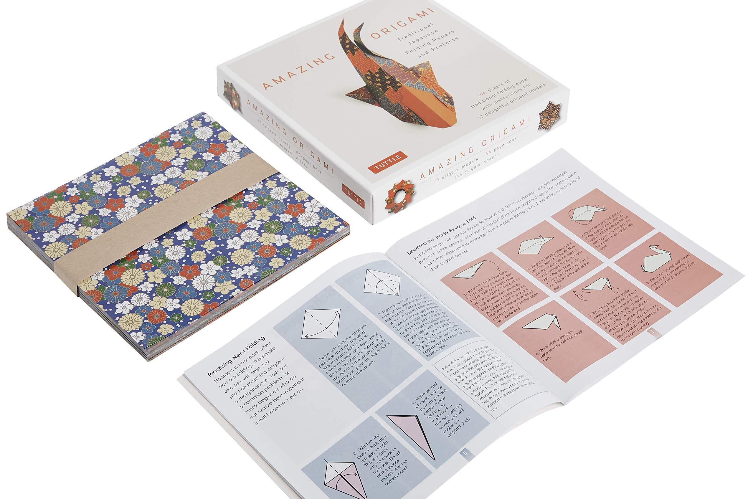 """A book titled """"Amazing Origami"""", open to show a folding pattern, next to colorful papers"""