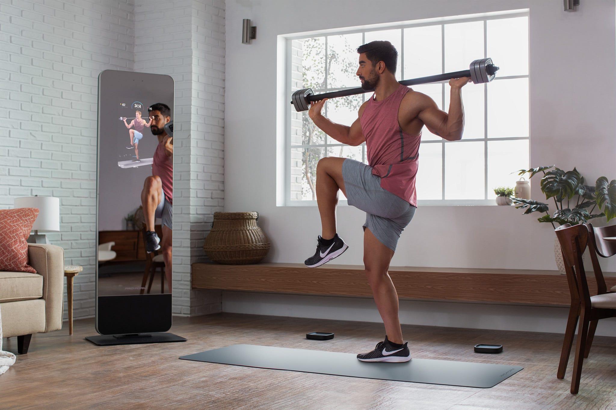 Мужчина тренируется со штангой перед фитнес-системой ProForm Vue.