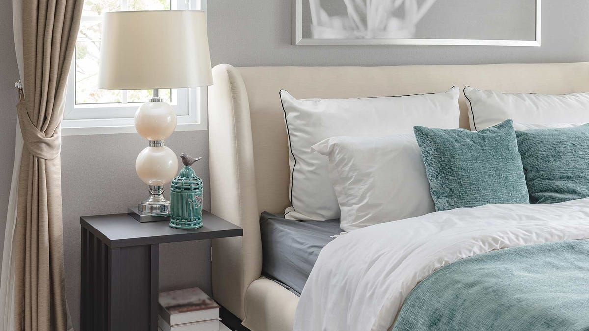 A brightly light bedroom with a bed heavily decorated with pillowed and a clean nightstand.
