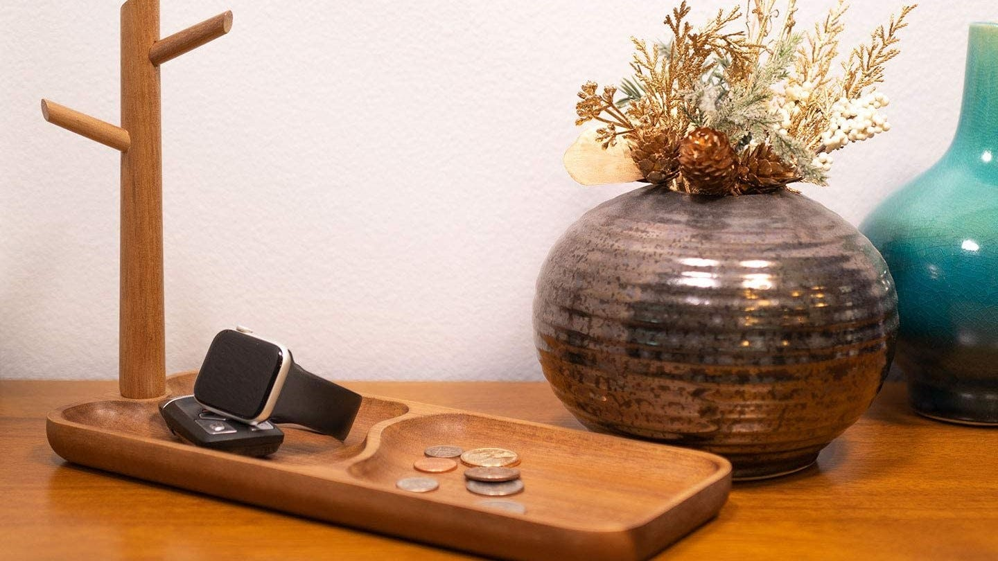 Trinket dish on a table with change and a watch in it.