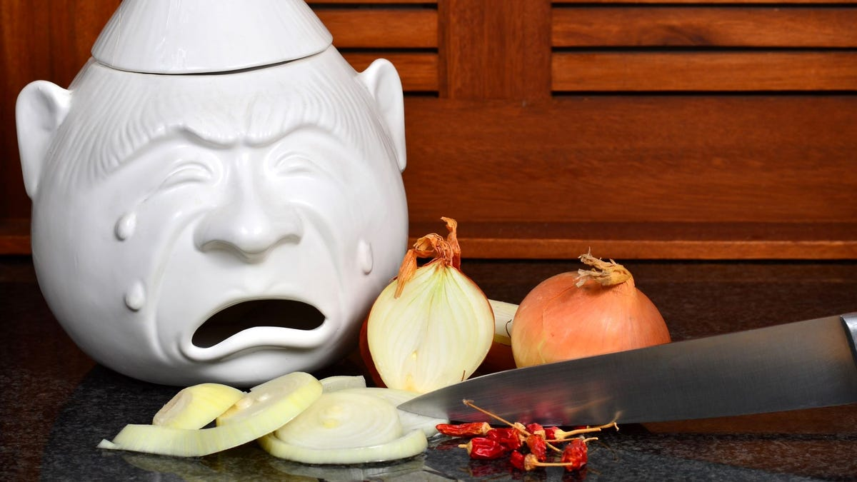 A ceramic cookie jar of a gnome crying next to a cutting board where someone is slicing onions with a knife.