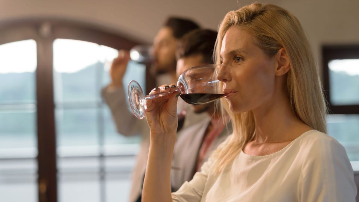 A woman and two men at a wine tasting.