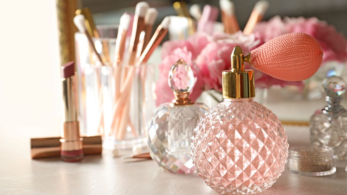 Perfume bottles, makeup brushes, and lipstick on a dressing table.