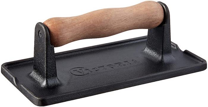 black cast iron grill press with a slightly ridged wooden handle
