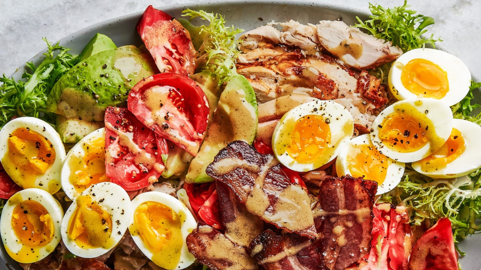 An oval plate filled with a heaping pile of greens topped with avocado and tomato slices, crispy bacon, and halved boiled eggs all topped with a bacon vinaigrette.