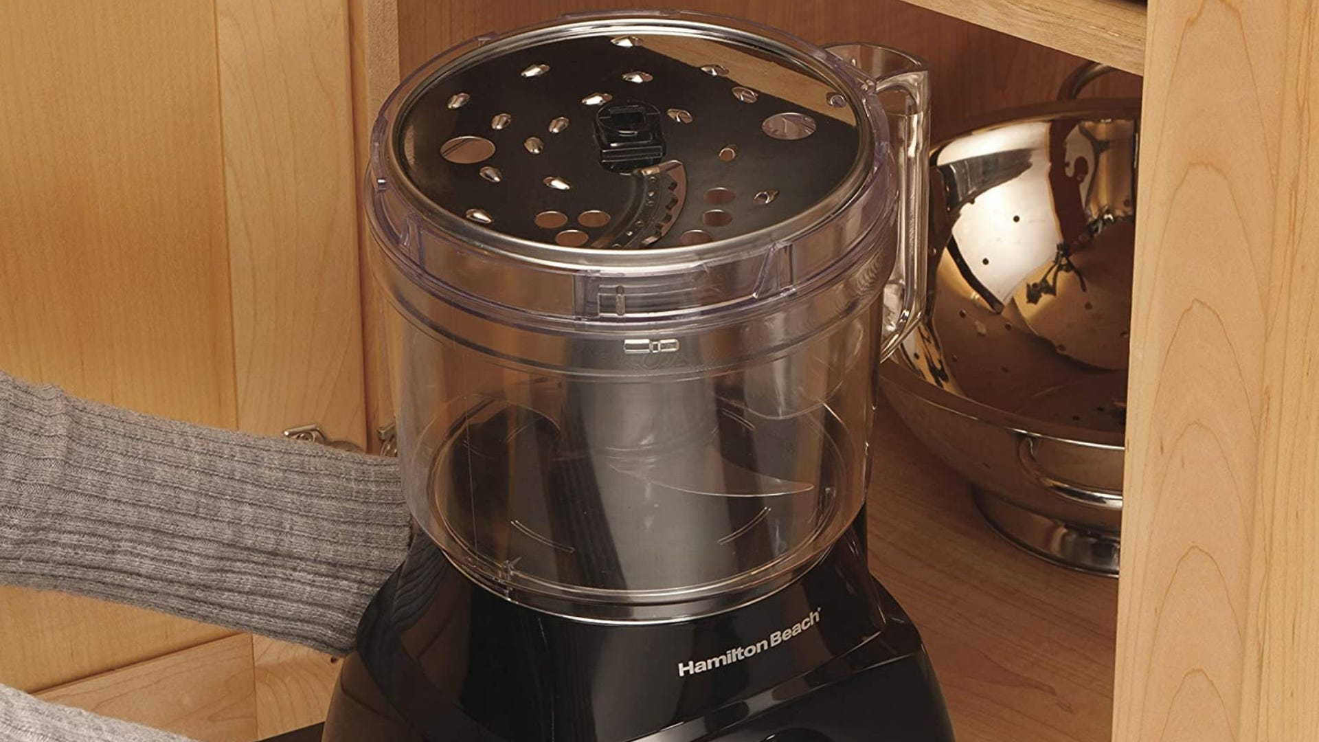 Person putting food processor in cabinet