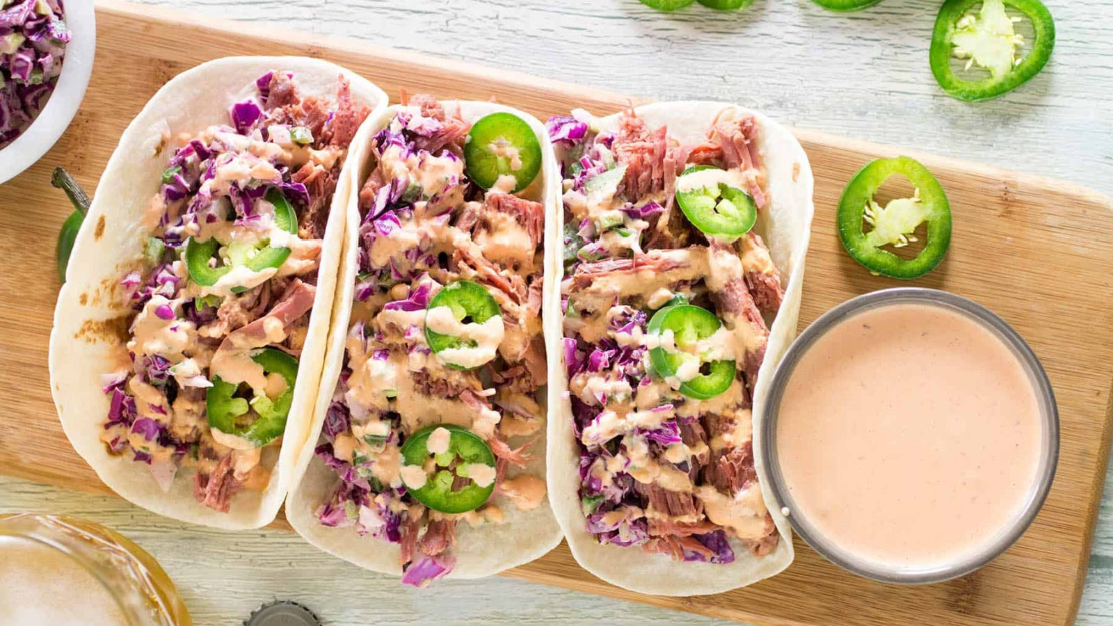 Three flour tortillas filled with shredded corned beef, topped with a slaw and Russian dressing on the side with sliced fresh jalapeno scattered nearby.