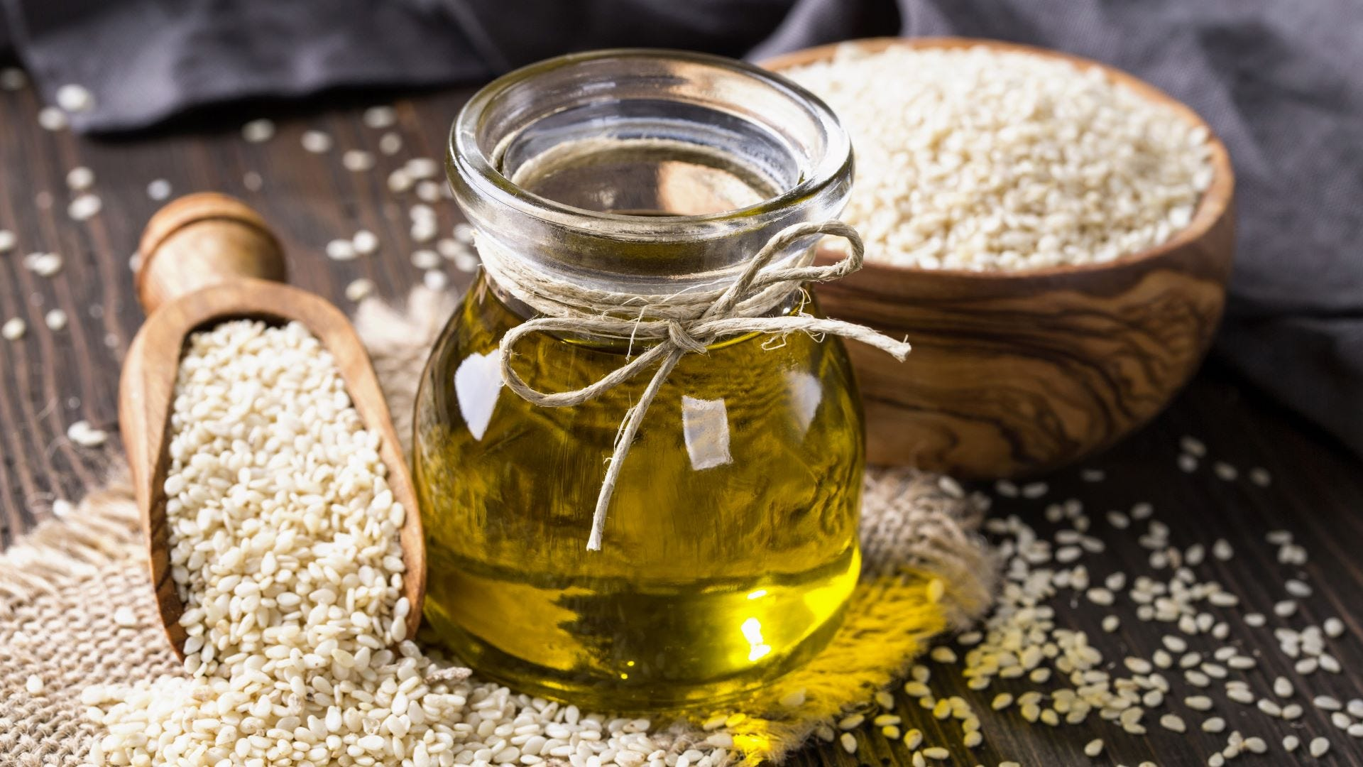 A jar of sesame seed oil surrounded by sesame seeds.