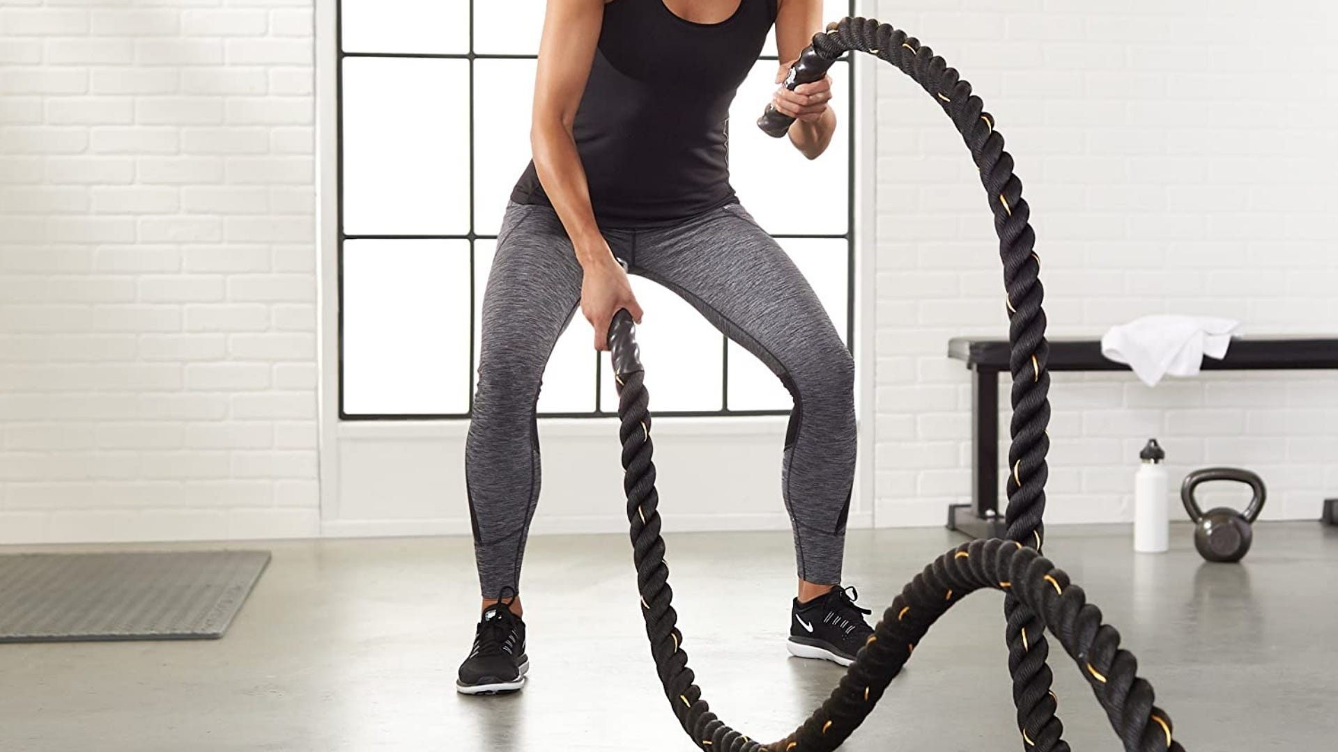 Woman is using battle ropes inside a gym.