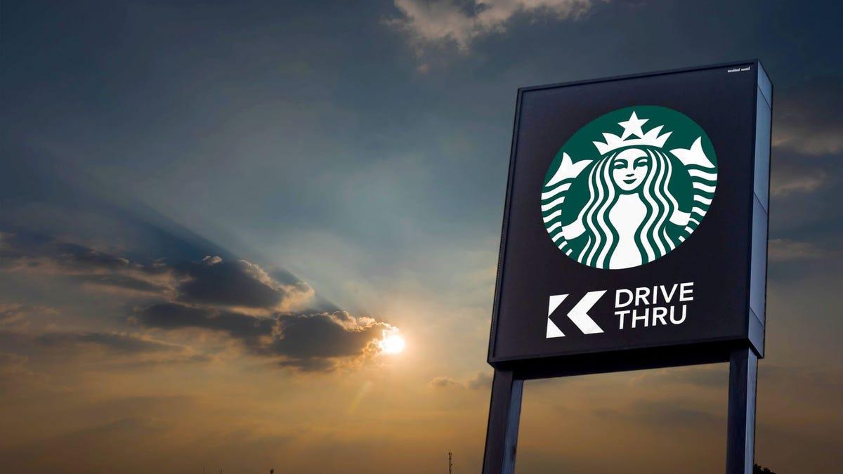 "The Starbucks Siren logo on a ""Drive Thru"" sign at sunset."