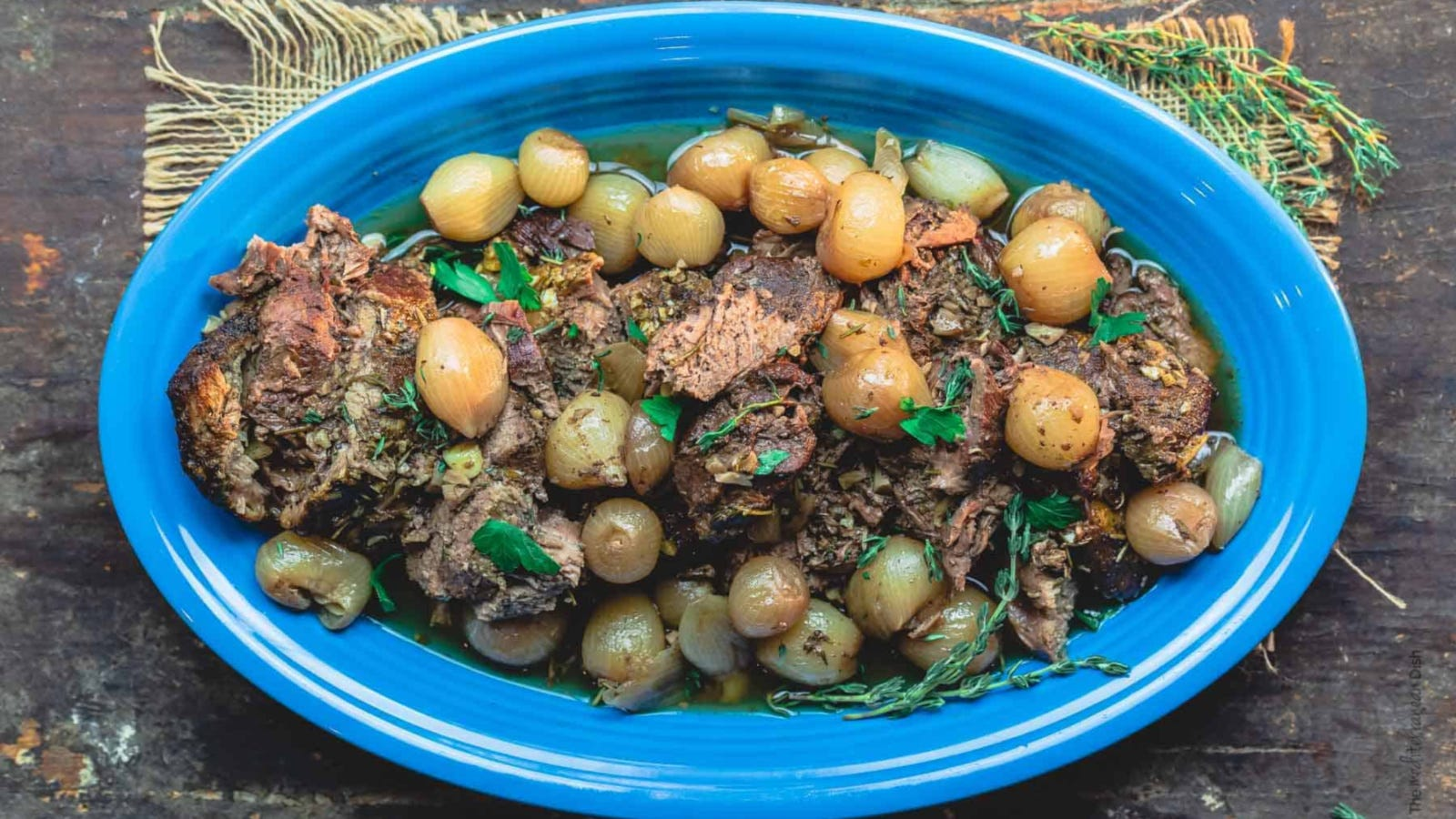 A blue oval plate topped with tender leg of lamb, served with pearl onions and fresh herbs.