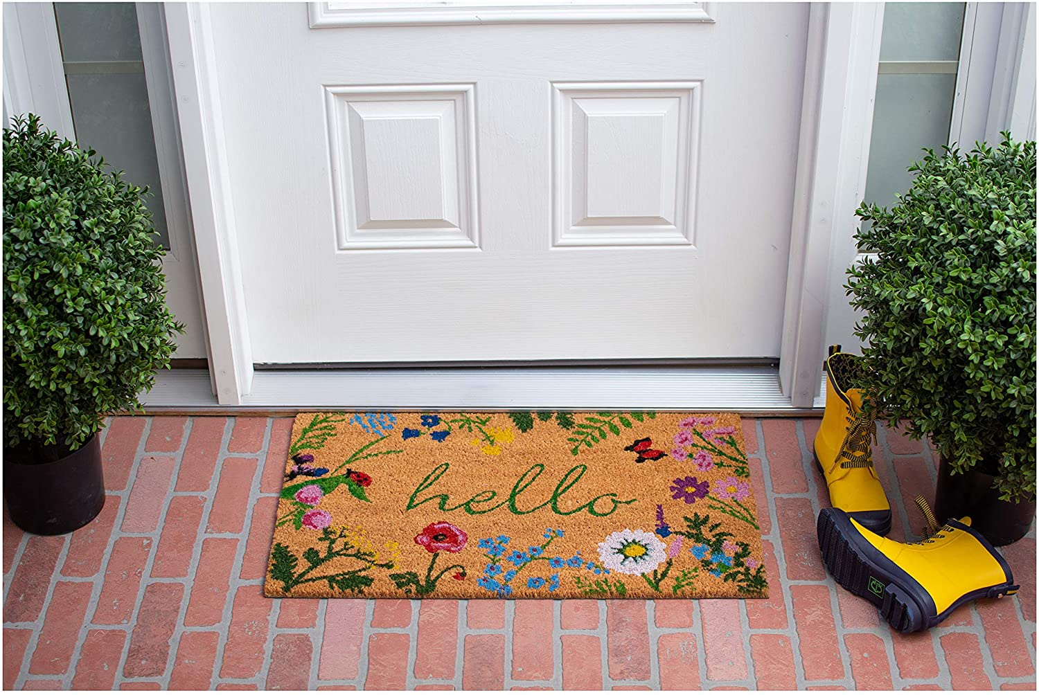 """A floral print doormat with script reading """"hello"""" on a brick patio in front of a white door"""