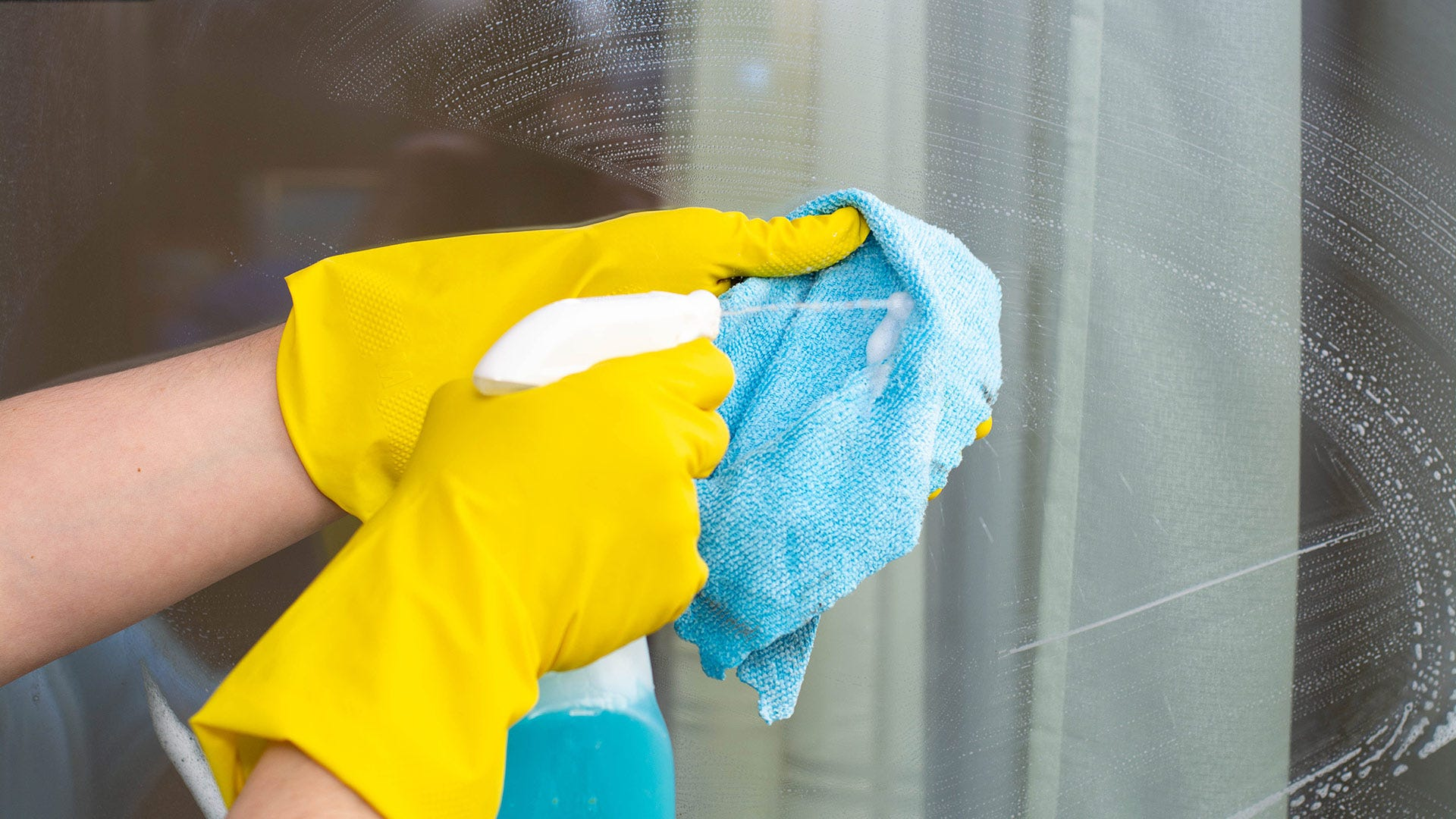 A person spraying window cleaner on microfiber cloth in front of a soapy window.