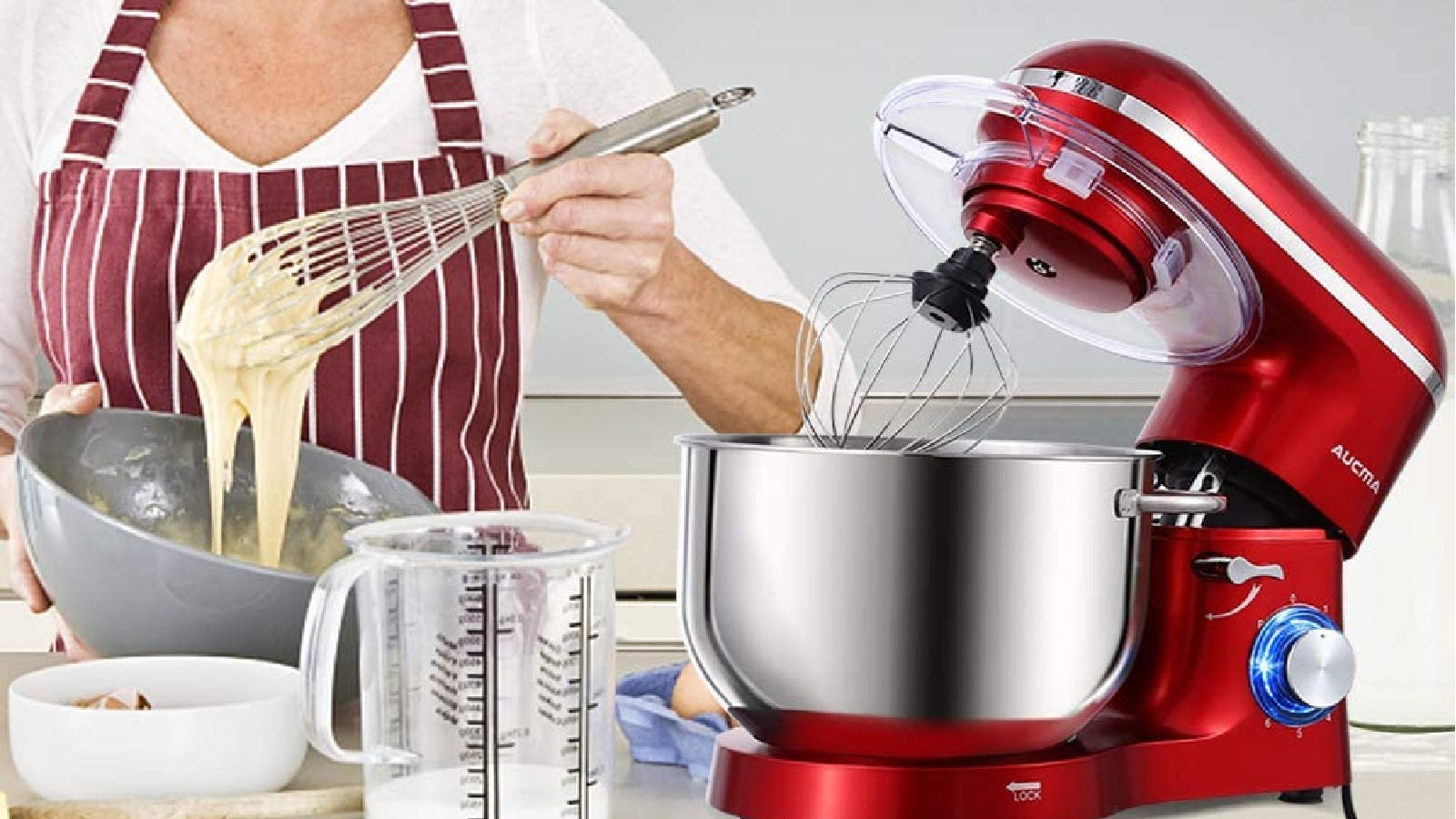 Someone mixing a batter with a red Aucuma stand mixer presented on the counter, with several ingredients and cooking gadgets surrounding it.
