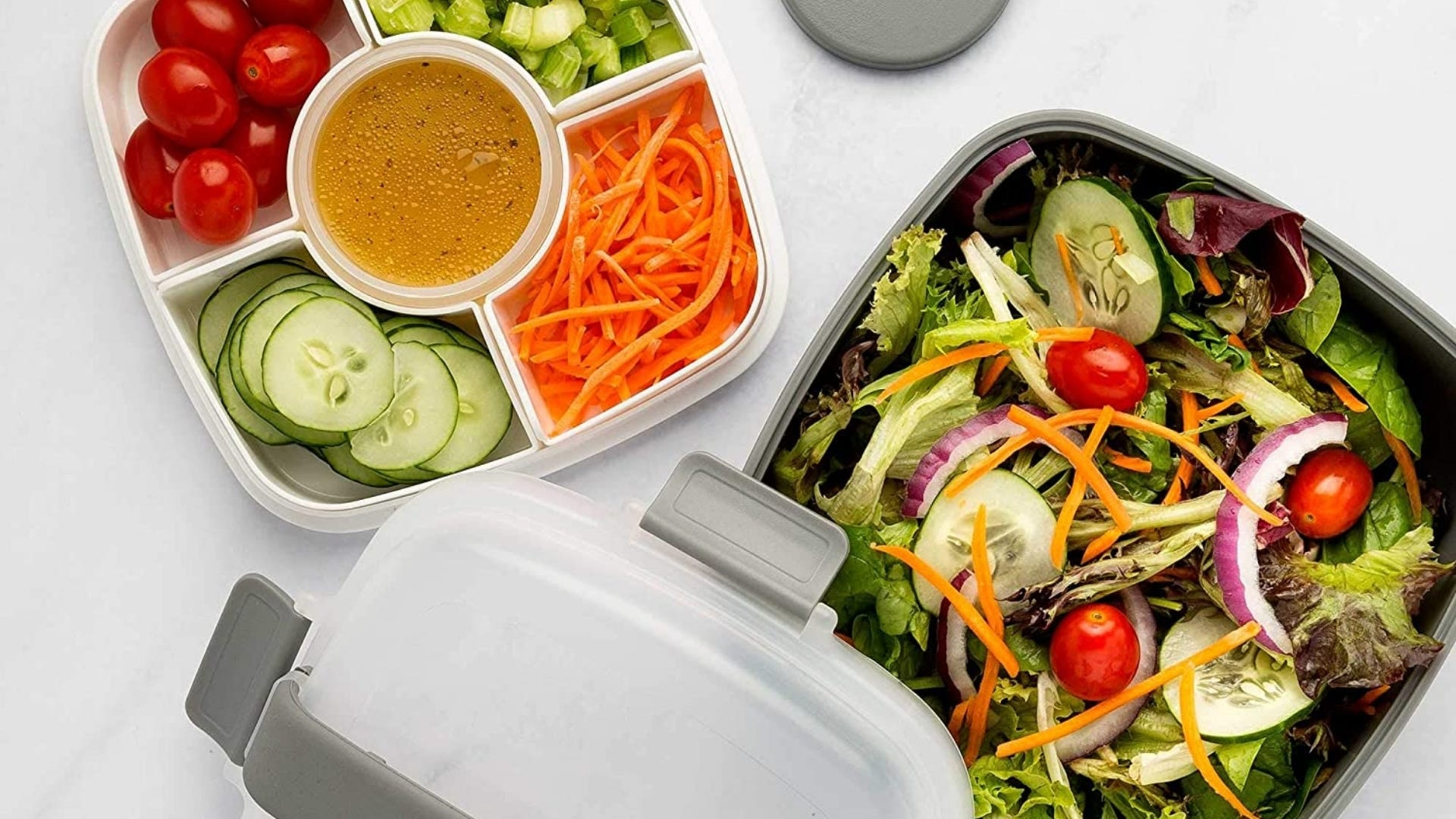 Salad container with salad in bowl and compartments of toppings