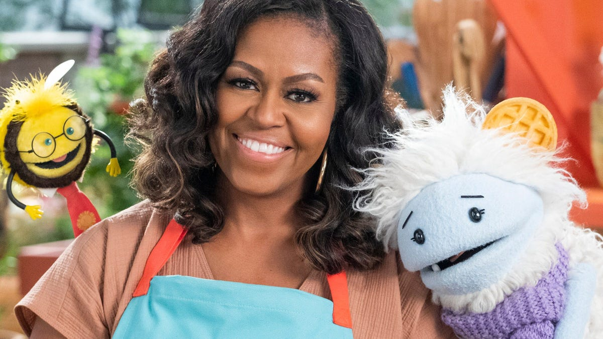 "Michelle Obama with two puppets from ""Waffles + Mochi."""