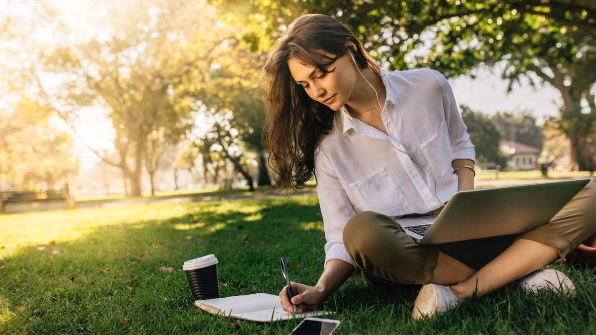 A woman sitting on the grass at a park with a laptop, and writing in a notebook.