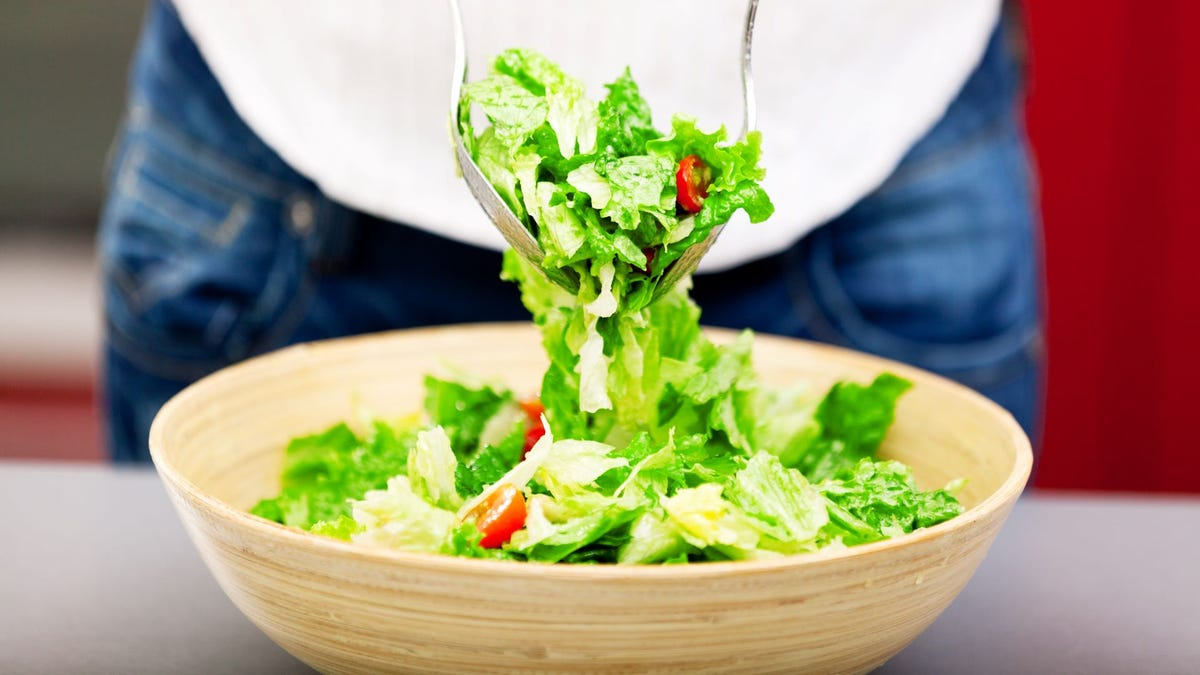 Someone tossing a salad in a bowl with tongs.