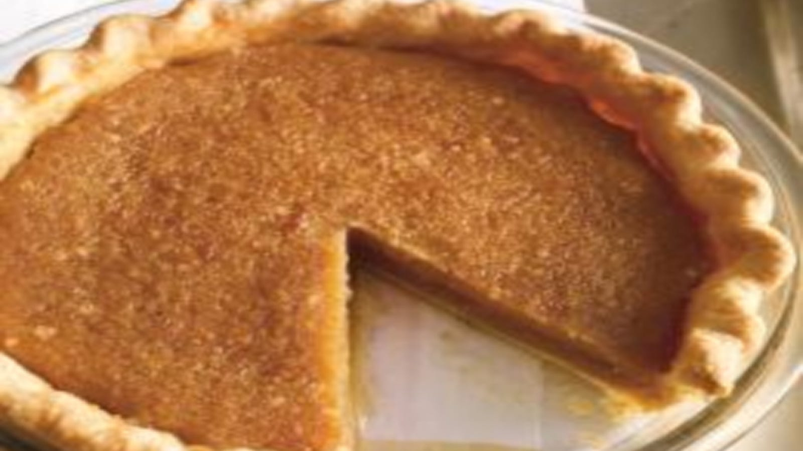 A warm maple syrup pie in a beautifully fluted pie crust, with one slice missing.