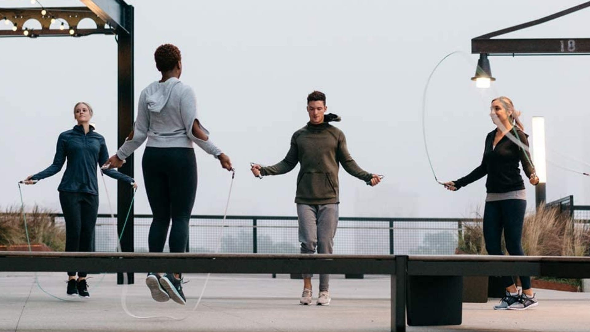 Four people are jumping rope outside.
