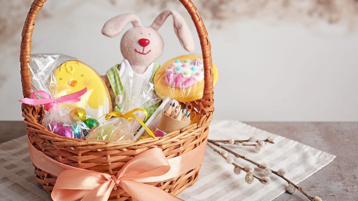 An Easter basket with a stuffed bunny, cookies, chocolate eggs, and Peeps in it sitting on a table.