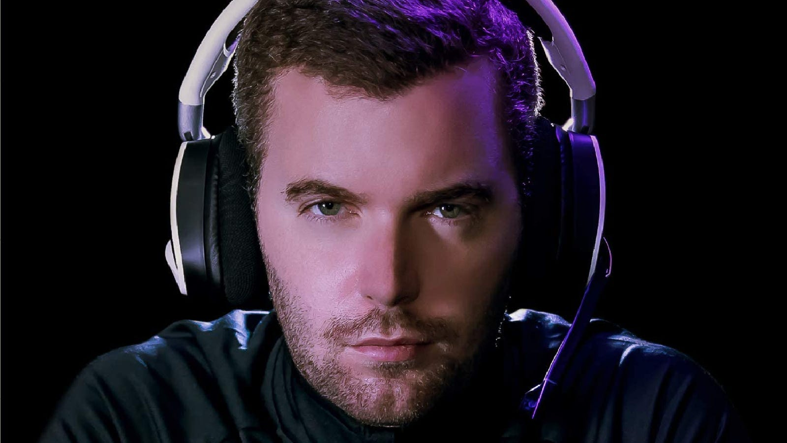 A man wears a gaming headset with a microphone in a dark room.
