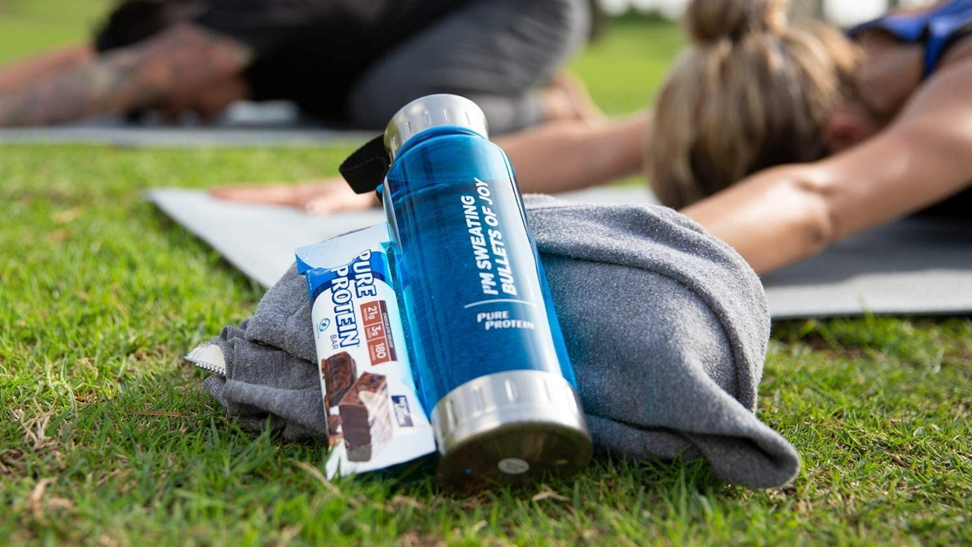 A protein bar sits next to a water bottle on the grass.