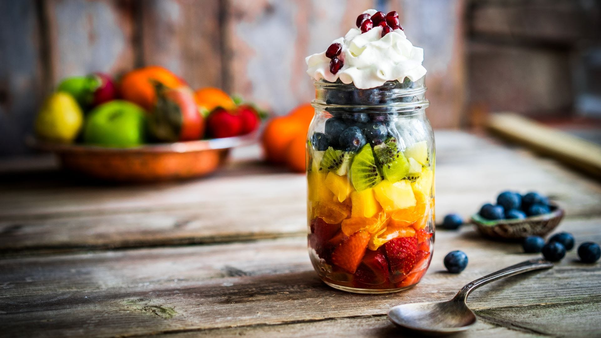 A fruit salad parfait in a jar topped with whipped cream and berries.
