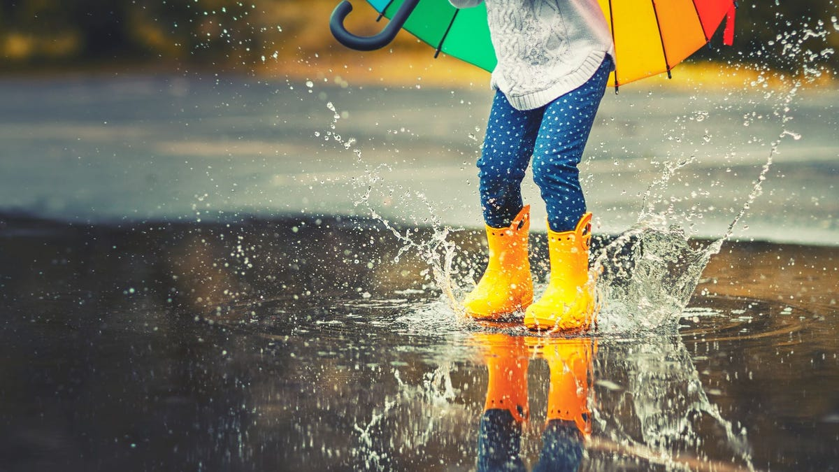 A child wearing yellow rubber boots jumping in a rain puddle.
