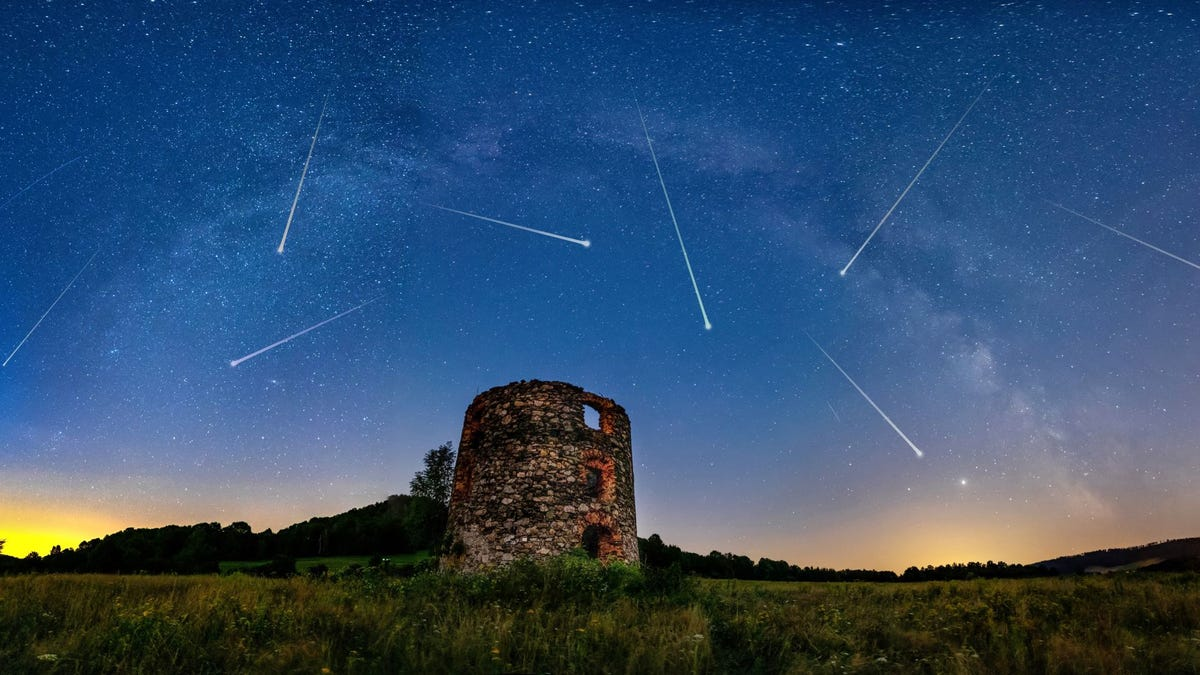 A meteor shower in a twilight sky above a ruin of a castle.