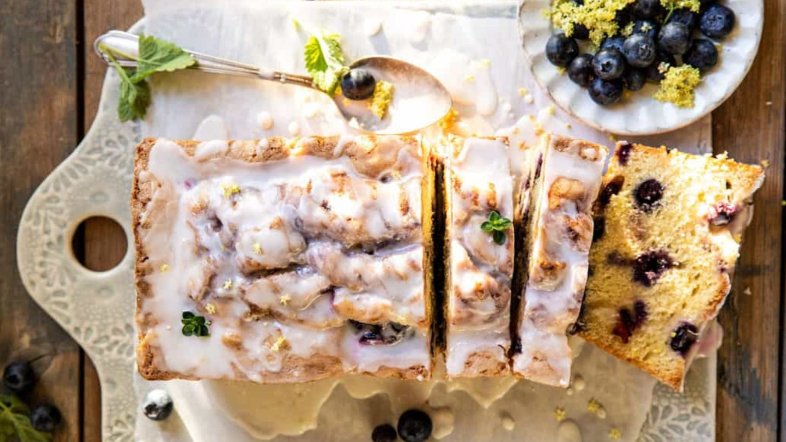 A loaf of blueberry lemon thyme cake with blueberries and a spoon coated with thyme glaze on the side.