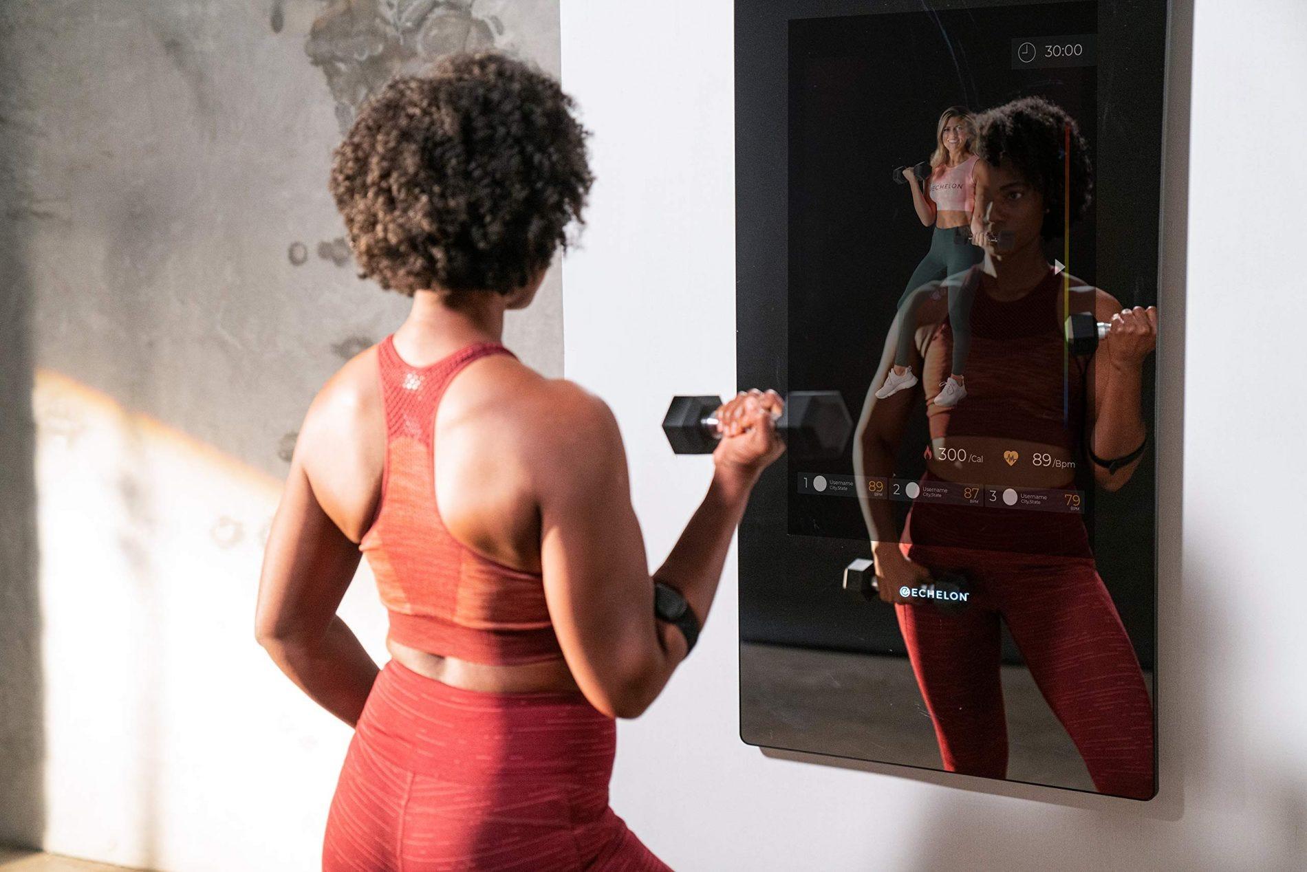 Женщина работает с гантелями перед фитнес-системой Echelon Reflect Touch.
