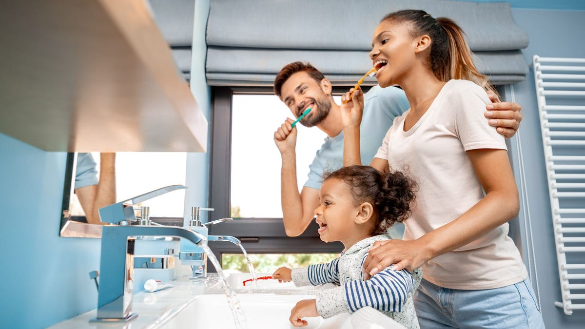 A man, woman, and little girl brushing their teeth.